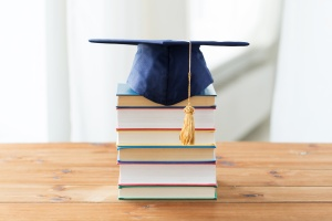 close up of books and mortarboard on wooden table